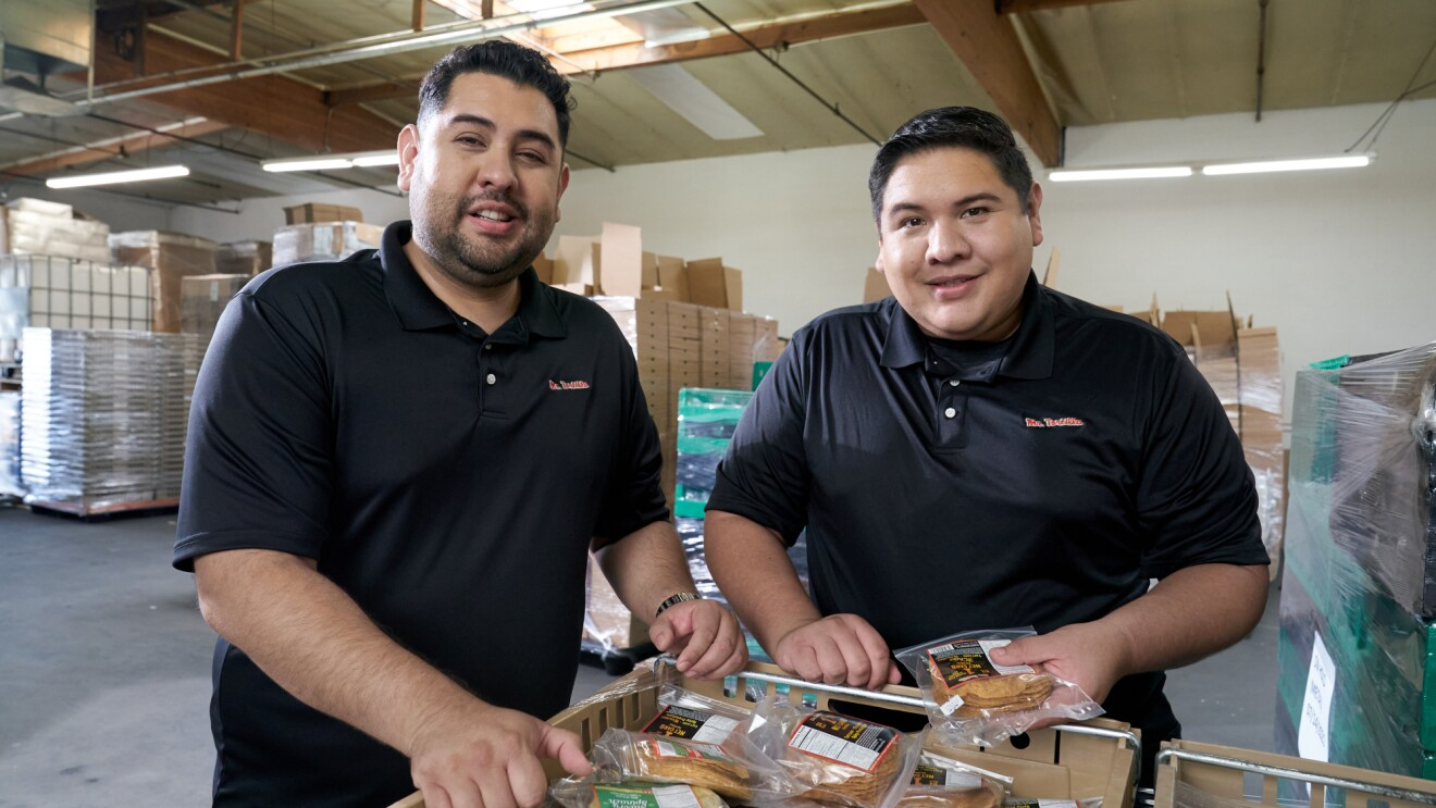 Anthony and Ronald stand side-by-side leaning on pallets of their packaged tortillas.