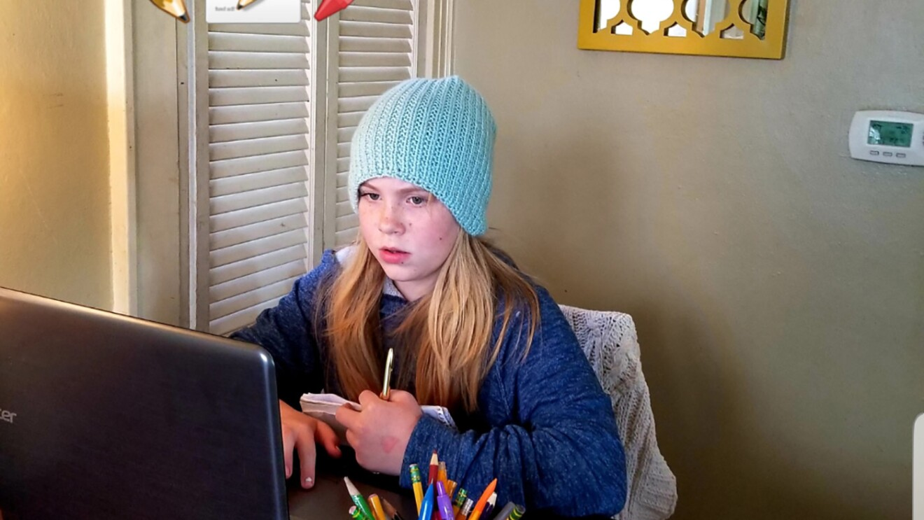 An elementary age student sits with their laptop computer in their home