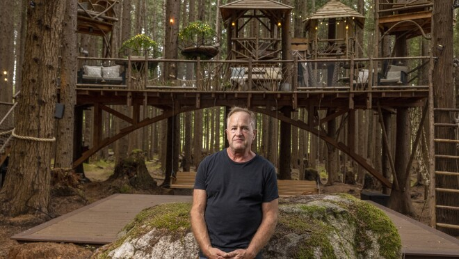 A man stands in front of a large rock, a large wooden structure, and a forest.