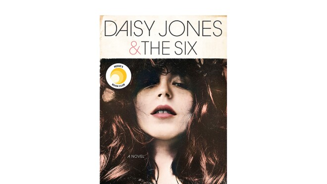 """A book cover for """"Daisy Jones & the six,"""" a novel by Taylor Jenkins Reid shows a young woman with long dark hair looking downward into the camera. The book background is an age-stained ivory, with all-caps font for the title and author's name."""