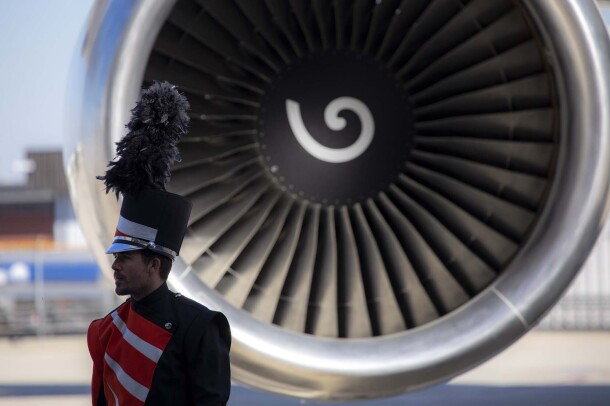 A man in marching band uniform, stands in front of a 767 turbine engine.