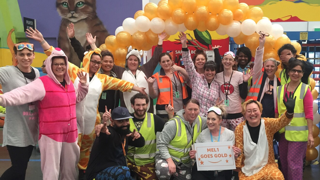 An image of Amazon employees wearing pajamas at work as a part of the Goes Gold campaign. They are standing in front of a balloon arch with gold and white balloons and a wall with a cat and a colorful background painted on it.