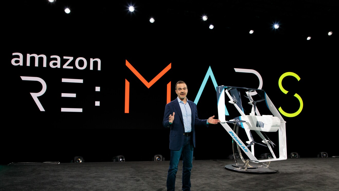 "Amazon CEO worldwide consumer, Jeff Wilke, stands on stage. Behind him ""re:MARS"" is seen. To his left is a new Prime Air drone."