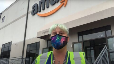 A woman wearing a mask and a safety vest stands in front of an Amazon fulfillment center