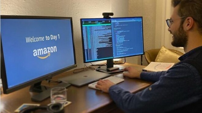 An image of a man smiling while working at his computer. One monitor has code on the screen and the other has the Amazon logo.
