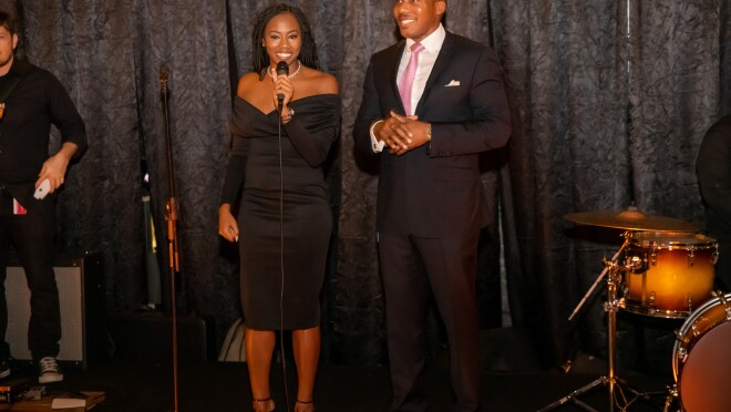 A man and a woman stand on a stage in formal wear in front of a microphone.