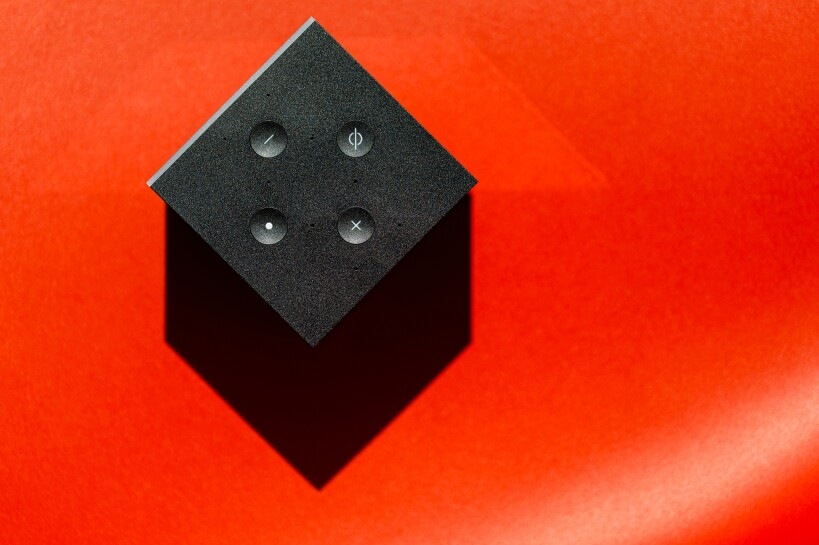 A top down magazine-style view of the Amazon Fire TV Cube on a solid red background