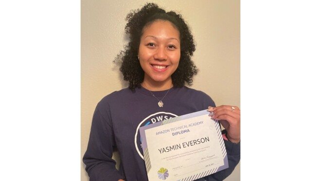 Yasmin Everson holds her ATA diploma as she smiles for the camera in front of a white wall. She has black curly hair and wears a navy long-sleeved shirt.
