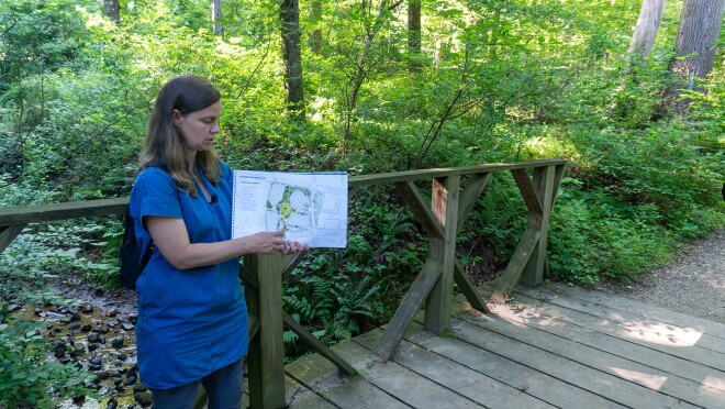 An image of a woman pointing to a blueprint of Amazon's HQ2 while standing on a bridge on a hiking trail with green trees surrounding her.
