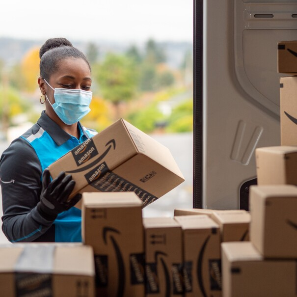 A woman wearing an Amazon delivery uniform picks up a package from the back of an Amazon truck full of packages.