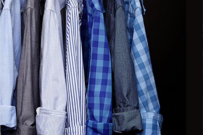Mens' button up shirts on hangers, lined up. Shirts are a variety of solids, striped and checkered patterns.