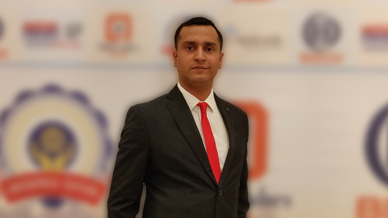 Jayant Jha, the CEO of Yantra stands across a banner in a formal suit