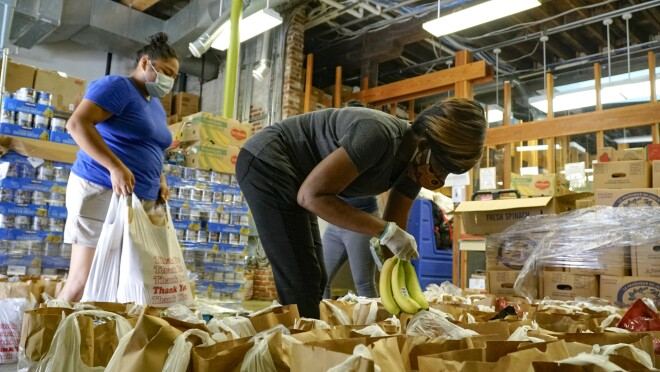 Two women load bags with fresh food in a warehouse space.