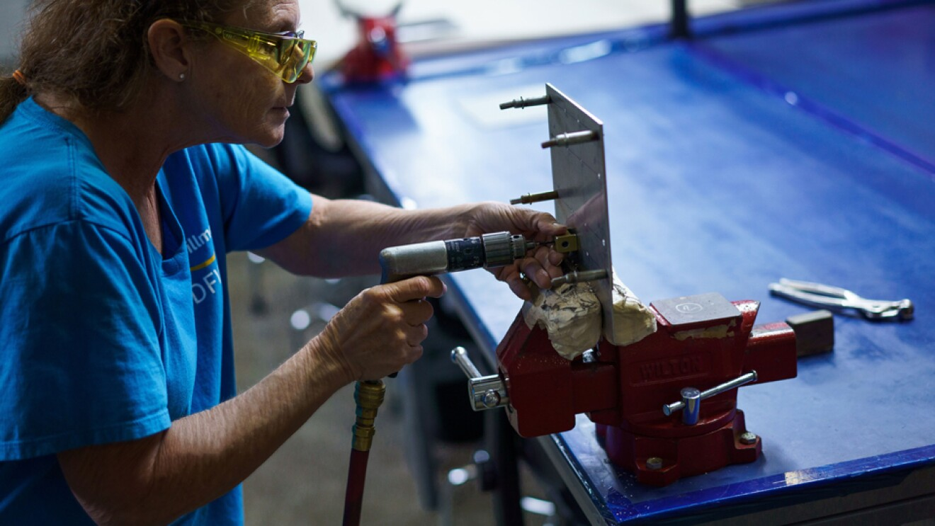 A woman in a blue T-shirt holds a tool and leans toward a workbench vise.