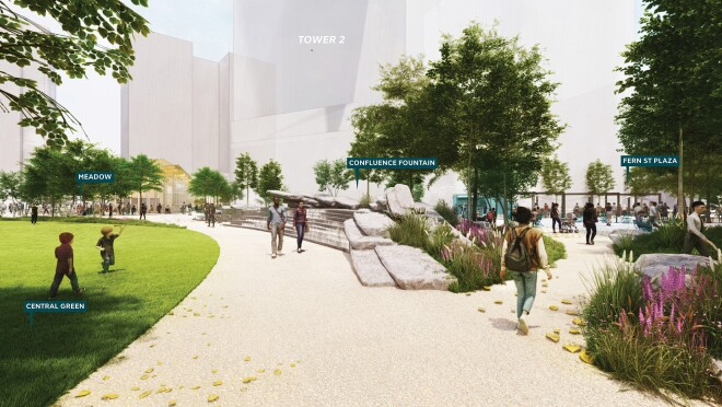 A rendering of the exterior of Amazon's HQ2. There is a large, paved walkway surrounded by green grass and trees with large buildings in the distance.
