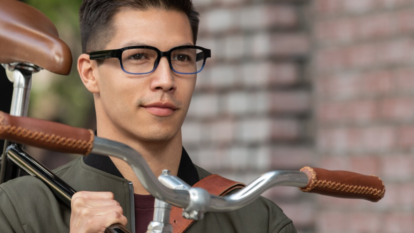 An image of a man wearing his Echo Frames glasses while walking down a sidewalk carrying his bike.