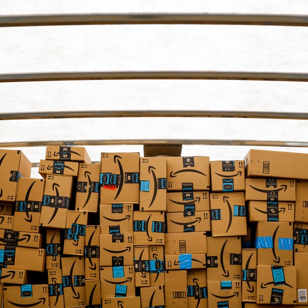 Amazon boxes stacked in a well-lit space inside a truck.