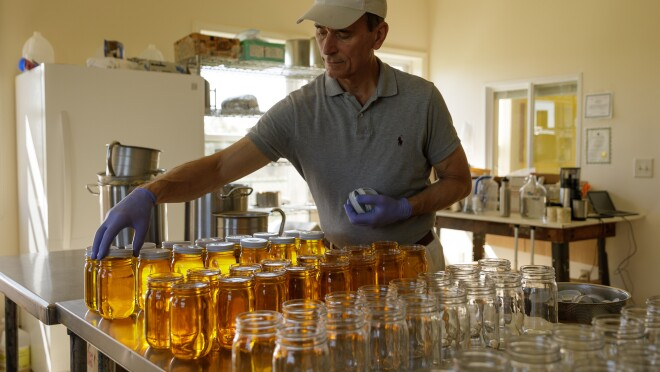 A small business owner readies jars of ghee, or clarified butter, for cooling.