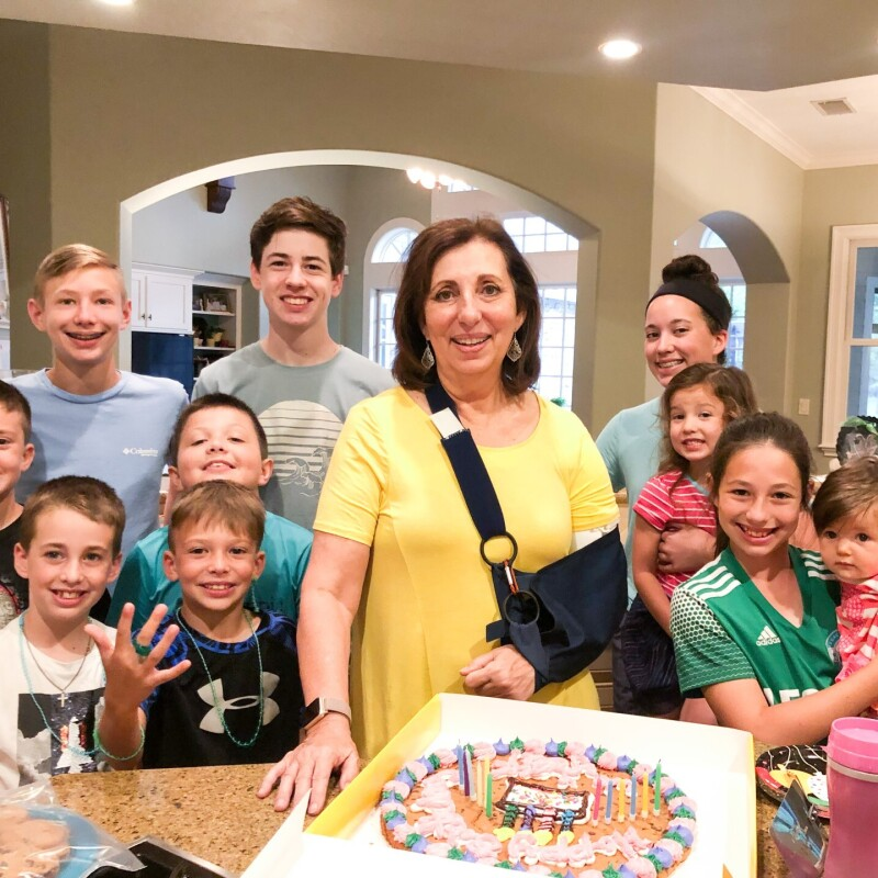 Rebecca in a sling supporting her left arm is surrounded by her ten grandchildren with a birthday cake in front of them.