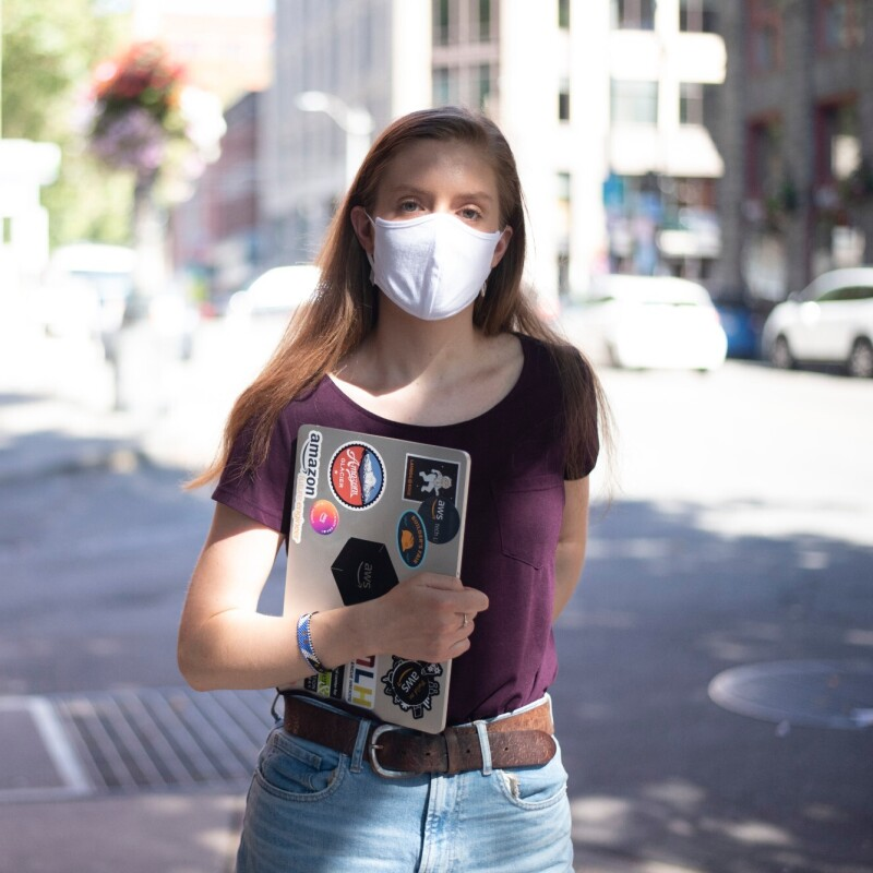 A woman stands on the street with a mask on, looking at the camera. She's holding a laptop with stickers related to Amazon and AWS.