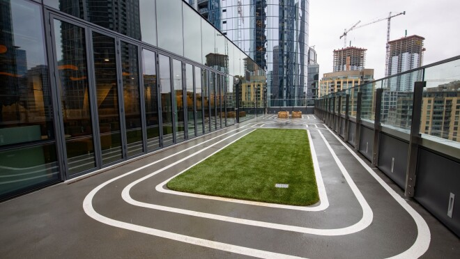 An image of an outdoor area on the rooftop of the Mary's Place Family Center in The Regrade. There is a small turf field with white track lines encircling it.