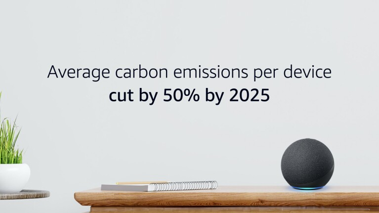 """A lifestyle image with an Echo Device, notebook, and plant, text says """"Average carbon emissions per device cut by 50% by 2025."""""""