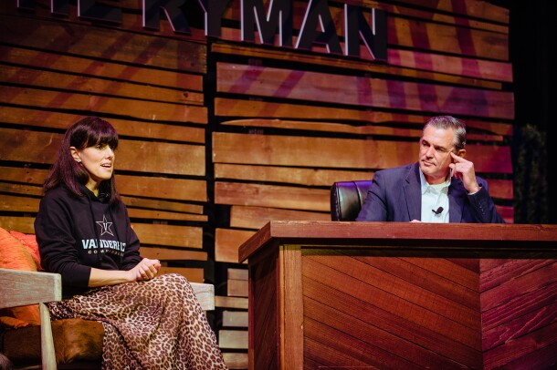Maria Renz of Amazon wears a Vanderbilt sweatshirt and animal print skirt. She's seated on a stage at The Ryman, next to a desk, with Kevin Omarah seated behind it. They engage in conversation.