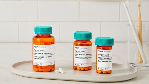 Three Amazon Pharmacy pill bottles sit on a white tray next to a glass with two toohbrushes in it.