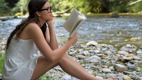 A girl with spectacles sitting and reading a book nearby a river