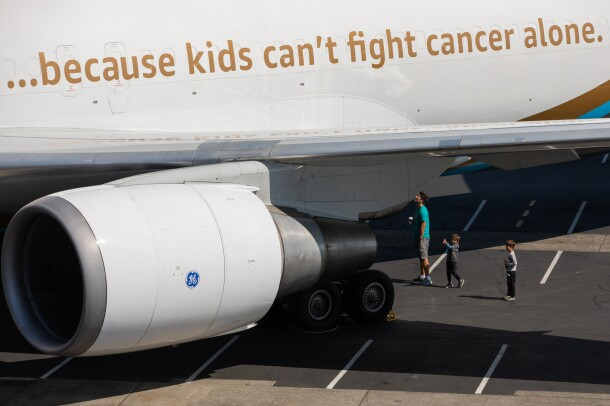 A father and his two small sons looking at the the underside of a large aircraft.