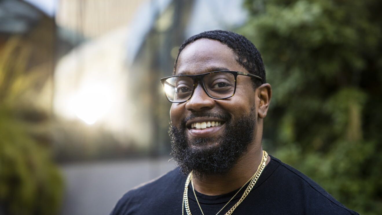 A smiling bearded man in a black T-shirt, glasses, and gold necklaces.