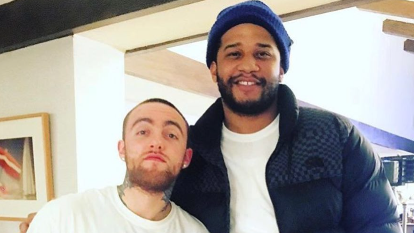An image of two men smiling for a photo--one is Timothy Hinshaw and one is Mac Miller.