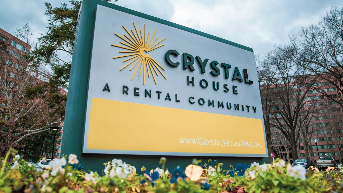 """An image of a sign in front of a building that reads """"Crystal House: A rental community"""" with the building's website (www.crystalhouseva.com) at the bottom."""