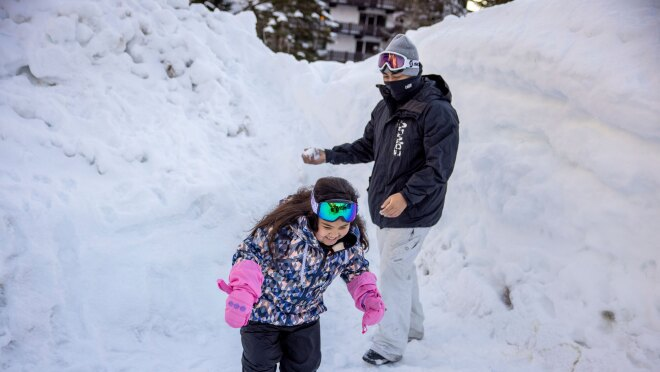 A dad and his daughter play in the winter snow.