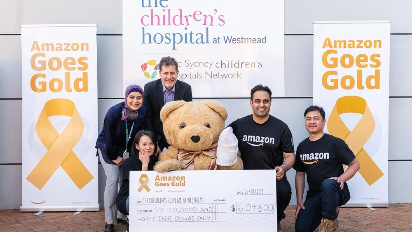 Amazon employees present a $6,048 check to The Children's Hosital at Westmead.
