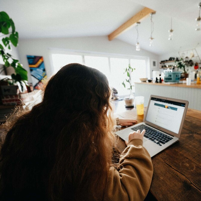 A woman works on her computer at her dining room table. In the background is a modern kitchen.