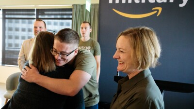 "A man wearing a ""warriors @ Amazon"" shirt hugs a woman. Next to him, another woman smiles. Behind him, two men stand near an Amazon military sign."