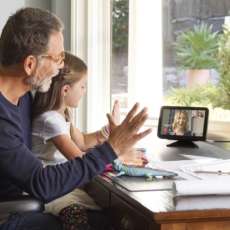 A little girl sits on a man's lap at a desk. They are both waving and looking at an Echo Show device, on which a woman is smiling and engaging with them.