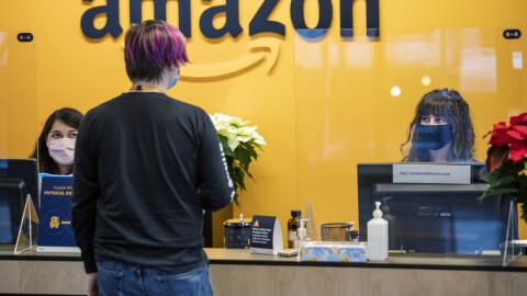 Amazon front desk employees speak with an Amazon employee. All are wearing masks, and there is a plexi divider between the receptionists and the employee. This photo was taken during the COVID-19 pandemic.