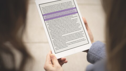 A person holds a Kindle device in their hands, while highlighting text with the Kindle Ruler.
