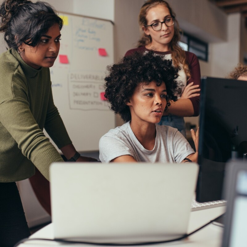 Four woman gather around a computer monitor in a classroom.