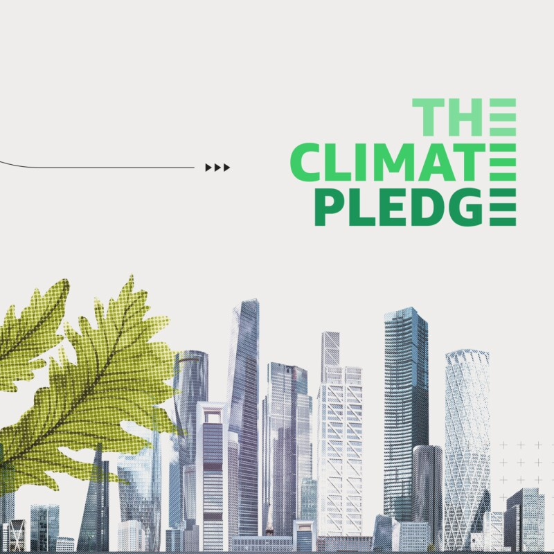 A city with tall buildings is the right backdrop of the image with The Climate Pledge in green font above it. To the left is green plant coming out from the city as tall as its buildings. To the left and behind the plant is a gray-toned drawing of the Earth.