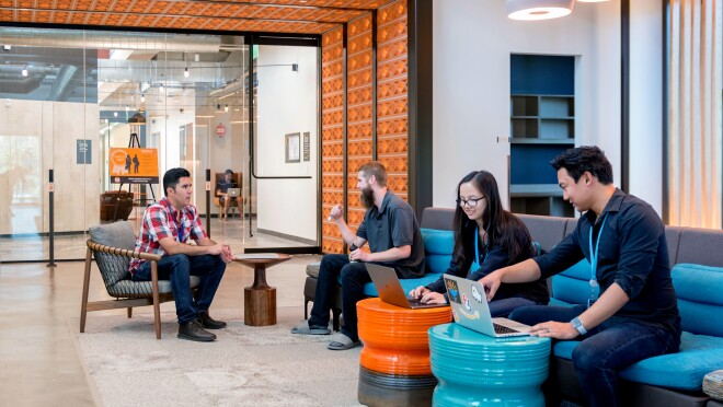 Amazon's San Diego tech hub, pairs of Amazonians sit in a common area, working on laptops and talking to one another.