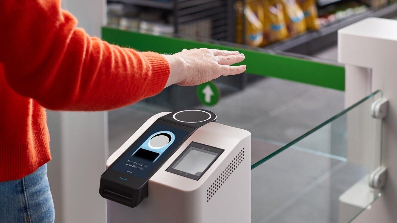 A person stands at a grocery entry gate with their hand suspended over a palm reading device.