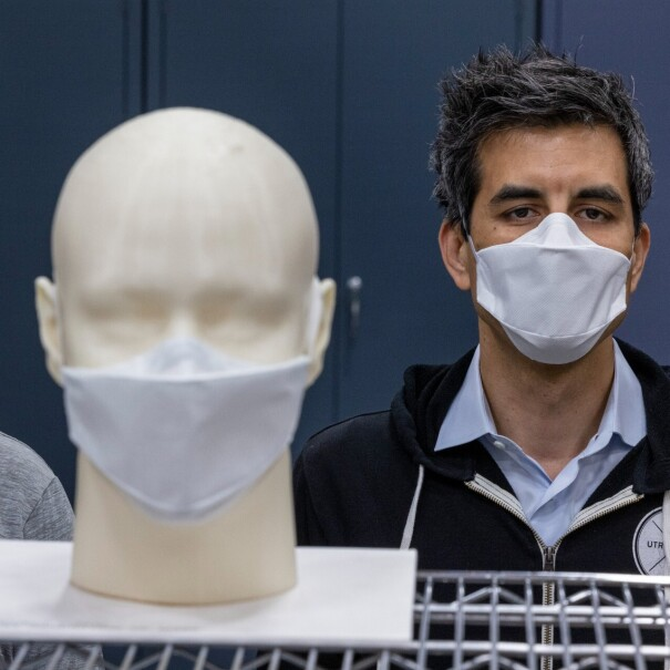 Two men wearing face masks stand behind a mask prototype.