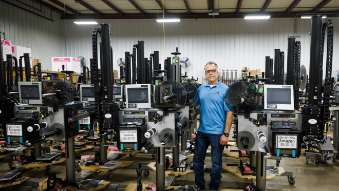 A man in a polo shirt and jeans stands among rows of tall metal machines.