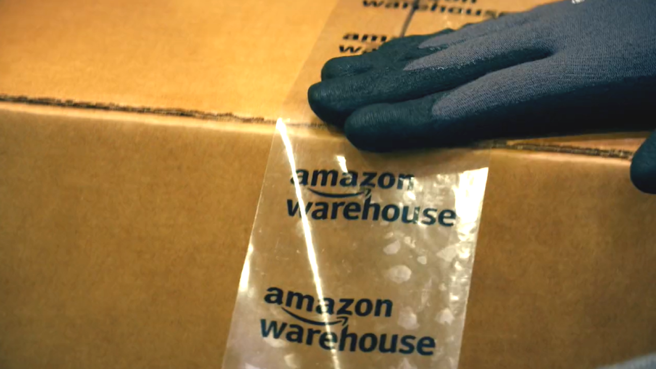Brown box being sealed with Amazon Warehouse tape.