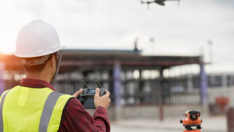 A man wearing a hardhat and yellow safety vest maneuvers a drone at an Amazon fulfilment centre site.