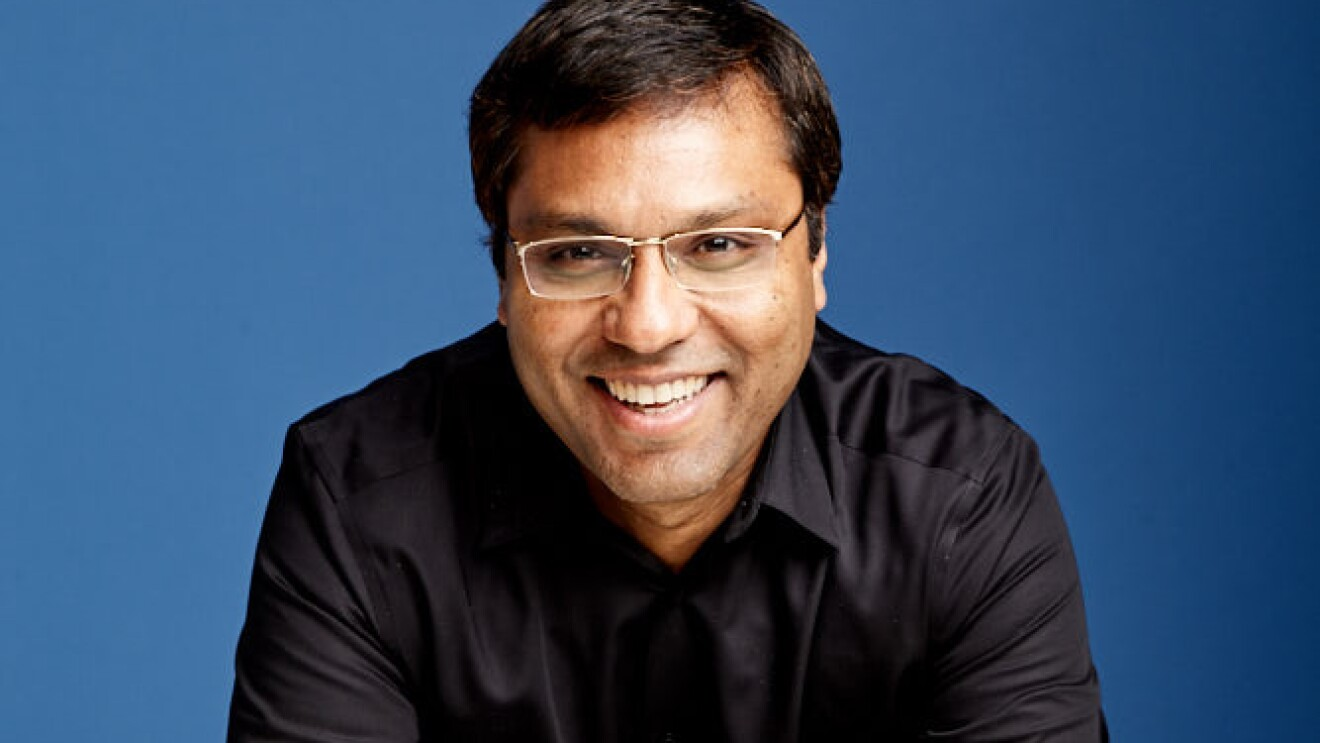 A portrait of Rohit Prasad, vice president and head scientist, Alexa AI. He is wearing a black shirt and is photographed against a blue background.
