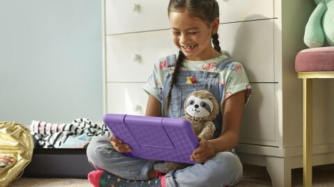 An image of a child sitting down, looking at a purple tablet and smiling. The tablet is an Amazon Fire HD 10 Kids Edition.